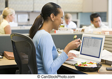 Businesswoman in cubicle eating sushi smiling