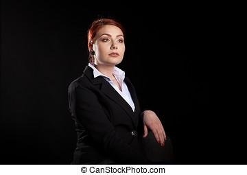Businesswoman in formal wear posing in studio on black...