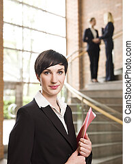 Businesswoman in front of two women in the stairs