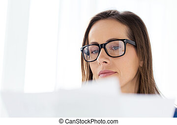 businesswoman in glasses reading papers at office