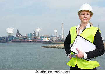 Businesswoman in hardhat and safety vest holding a clipboard outdoors