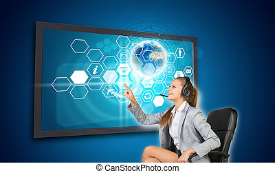 Businesswoman in headset pressing touch screen button on virtual interface