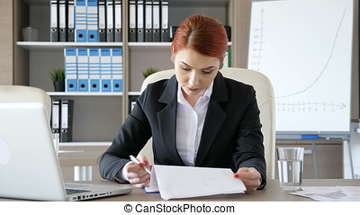 Businesswoman in her office signing some papers. Corporate...