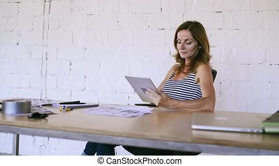 Businesswoman in her office with a tablet. - Mature...