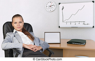 Businesswoman in office chair, with her hands clasped over stomach
