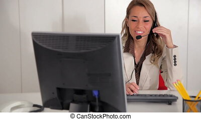 Mid adult woman with headset talking on the phone and typing on keyboard in office