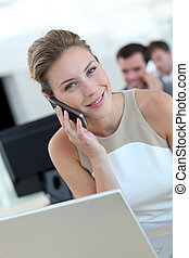 Businesswoman in office talking on mobile phone