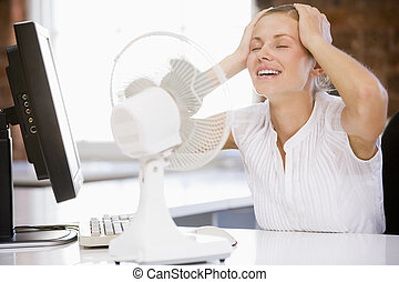 Businesswoman in office with computer and fan cooling off