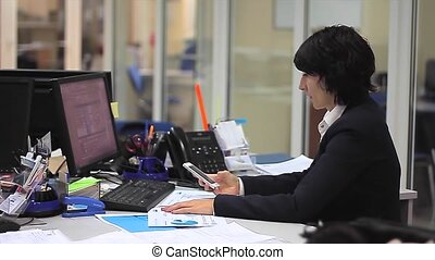 Businesswoman in office with computer and smartphone