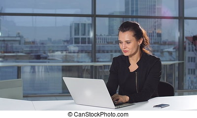 Businesswoman in office with laptop computer.