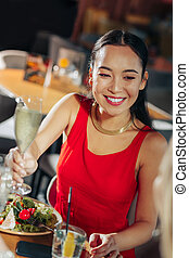 Businesswoman in red dress eating salad and drinking champagne