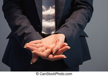 Businesswoman in suit holding her hands out