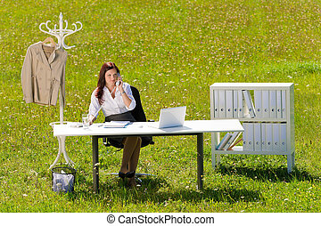 Businesswoman in sunny meadow calling nature office - Young...