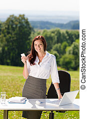 Businesswoman in sunny nature office calling