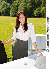 Businesswoman in sunny nature office smile