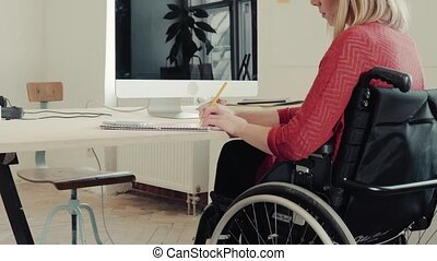 Businesswoman in wheelchair at the desk in her office. -...