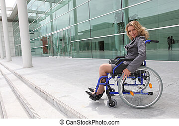 Businesswoman in wheelchair outside office block
