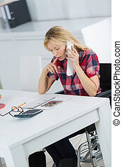 businesswoman in wheelchair working at her desk
