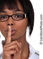 Businesswoman indicating quiet