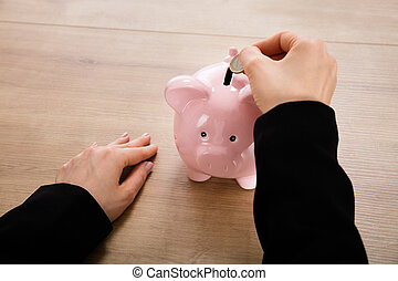 Businesswoman Inserting Coin In A Piggybank