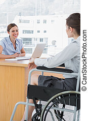 Businesswoman interviewing disabled job candidate in her...
