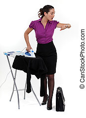 Businesswoman ironing and looking at the time