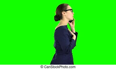 Businesswoman is going to a meeting and talking on the phone. Green screen. Side view