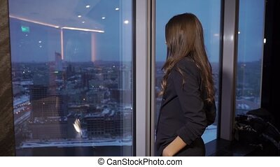 Businesswoman is looking through the window