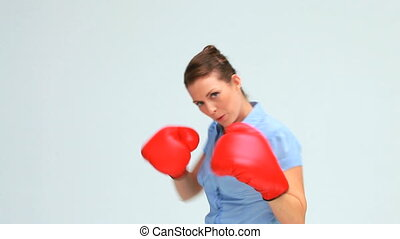Businesswoman kicking and boxing against white background