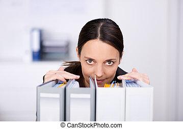 businesswoman, kijken over, verzamelmappen, in, kantoor