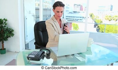 Businesswoman late for a meeting picking up the phone in a...