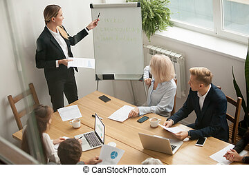 Businesswoman leader giving presentation explaining team goals a