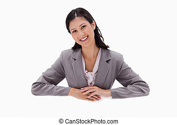 Businesswoman leaning on blank wall