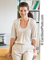 Businesswoman leaning on office desk