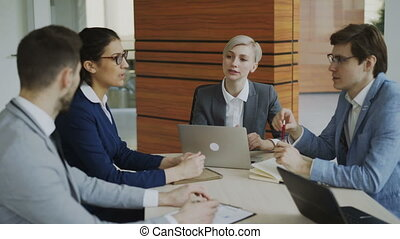 Businesswoman listening her colleagues explaining business project sitting at the table in modern office