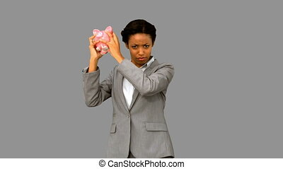 Businesswoman listening to an empty piggy bank on grey...