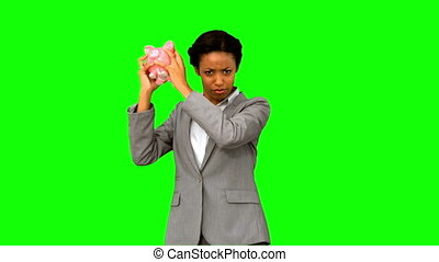 Businesswoman listening to an empty piggy bank on green...