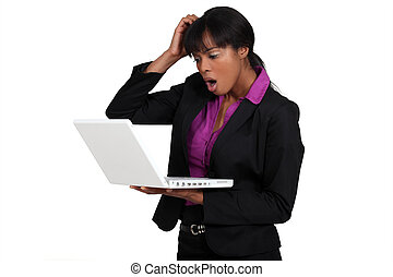 Businesswoman looking alarmed at her laptop
