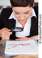Businesswoman looking at a chart with a magnifying glass