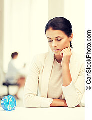 businesswoman looking at alarm clock - business and time...