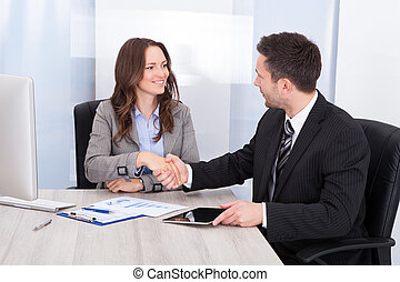 Looking At Businessman While Shaking Hand At Office Desk