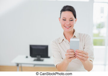 Businesswoman looking at cellphone in office