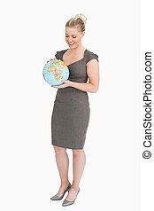 Businesswoman looking at globe in her hands