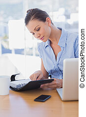 Businesswoman looking at her diary and smiling