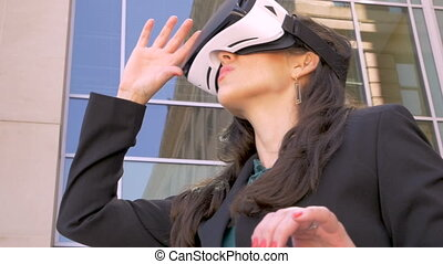 Businesswoman looking at her hands in a virtual reality world through goggles