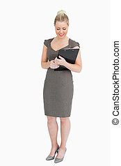 Businesswoman looking at notepad in her hands
