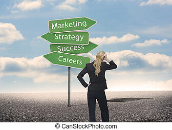 Businesswoman looking at signposts