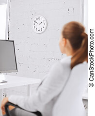 businesswoman looking at wall clock in office - business,...