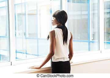 Businesswoman looking at window in office