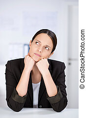 Businesswoman Looking Away While Leaning On Desk